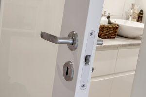 Hvit dør inn til bad. Lås, håndtak, nøkkelhull.